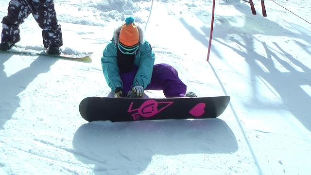 スノーボードを座って履いているところ