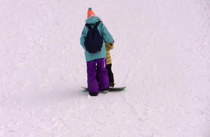 子どもにスノーボードを教えているママ2