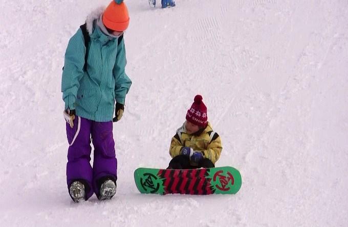子どもにスノーボードを教えているママ