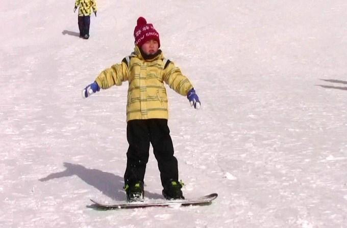 子どもにスノーボードを教えるパパ2