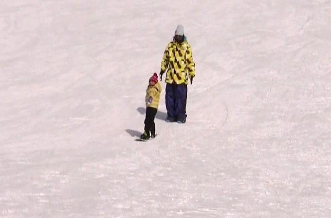 子どもにスノーボードを教えるパパ1