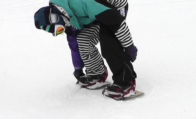 セパレートスノーボード「ニコ」でビンディングを締めているところ